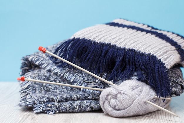 Schals und garnstränge mit metallstricknadeln auf grauen brettern und blauem hintergrund. strickkonzept.