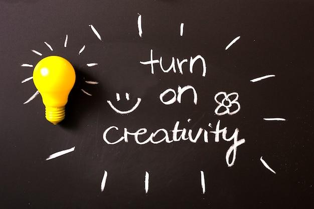 Schalten sie den kreativitätstext ein, der mit kreide auf tafel mit gelber glühlampe geschrieben wird