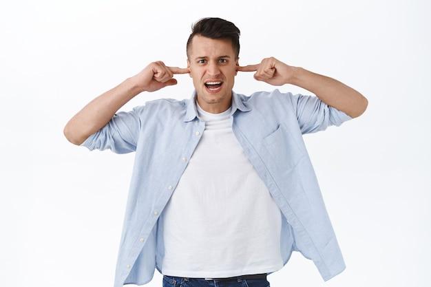 Schalten sie die lautstärke aus. porträt eines verärgerten, belästigten, gutaussehenden mannes sieht gereizt aus, schließe die ohren mit den fingern von störenden geräuschen, lauter musik oder nachbarn, weiße wand