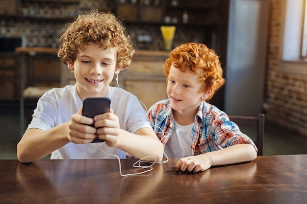 Schalten sie diesen ein. entzückende aufnahme von zwei kindern unterschiedlichen alters, die nebeneinander sitzen und ihre aufmerksamkeit auf einen bildschirm eines smartphones richten, während beide zu hause musik hören.