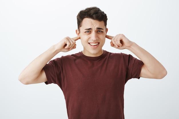 Schalten sie diesen nervigen ton aus. gestörter unzufriedener kaukasischer männlicher mitarbeiter im roten t-shirt