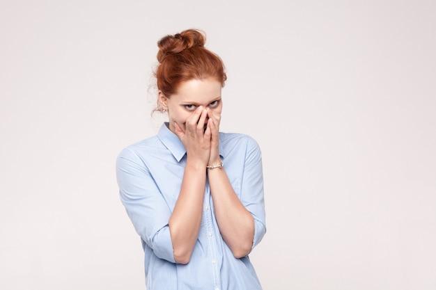 Scham und lügner-konzept. rothaarige frau, die den mund mit beiden händen bedeckt, die ein geheimnis und ein kleines lächeln halten. schöne rothaarigefrau im blauen hemd. isolierte studioaufnahme auf grauem hintergrund.