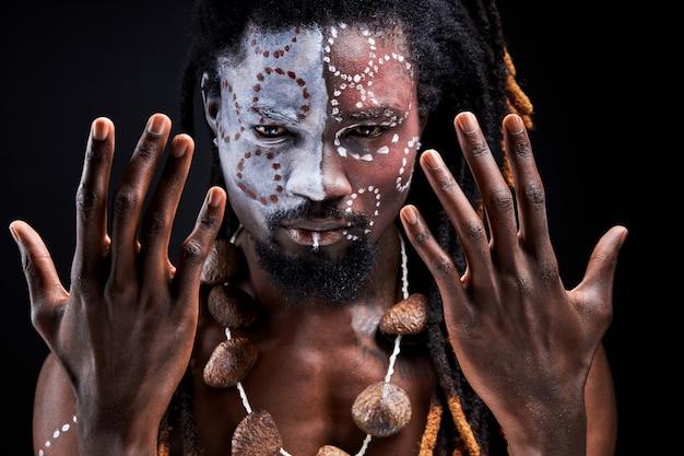 Schamanischer mann steht bei ritualen, spreizt hände, porträt eines schwarzen mit ethnischem make-up isoliert