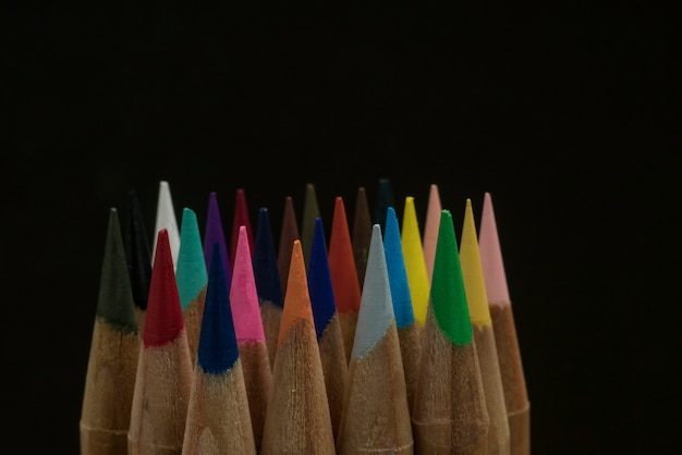 Scharfe buntstifte auf einem schwarzen hintergrund. kopieren sie platz