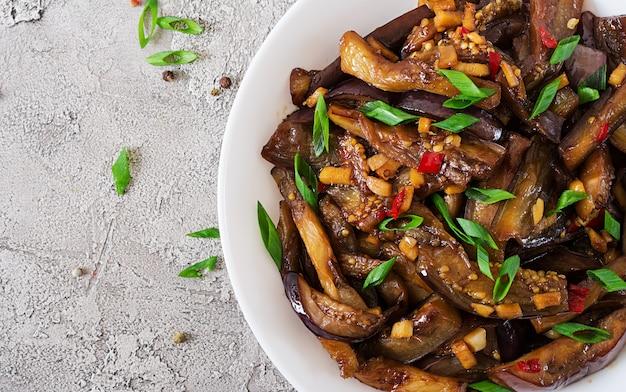 Scharfe eintopfaubergine im koreanischen stil mit frühlingszwiebeln. aubergine sautieren. veganes essen. flach liegen. ansicht von oben
