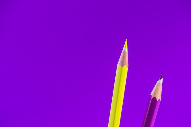 Scharfe farbige bleistifte auf einem violetten hintergrund mit platz für text