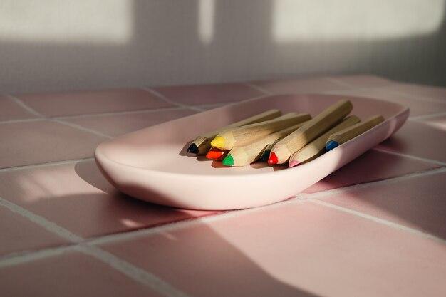 Scharfe holzfarbstifte in einem tablett auf weißem und rosafarbenem fliesenboden mit kopierraum.