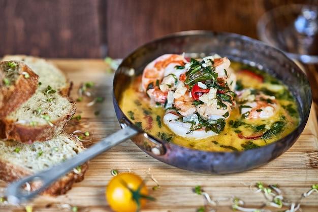 Scharfe knoblauchchili garnelen shrimps auf bratpfanne mit zitrone und koriander