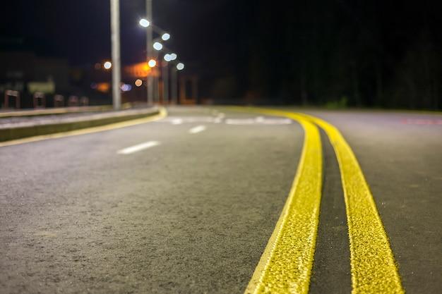 Scharfe kurve der breiten modernen glatten leeren asphaltlandstraße scharf mit heller weißer und doppelter gelber markierungszeichenlinie. geschwindigkeit, sicherheit, komfortables reisen und professionelles straßenbaukonzept.
