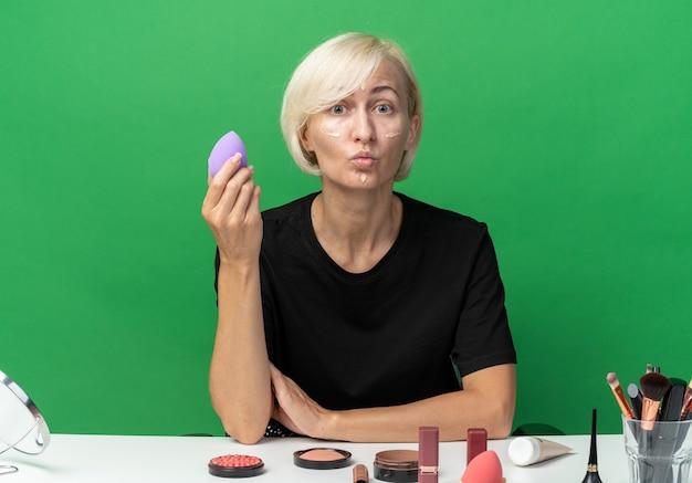 Scharfe lippen verwirrt junges schönes mädchen sitzt am tisch mit make-up-tools, die ton-up-creme auftragen, die einen schwamm isoliert auf grünem hintergrund hält