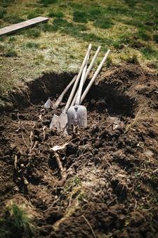 Scharfe schaufeln auf bebautem bauernhoffeld, rasen im frühjahr landend