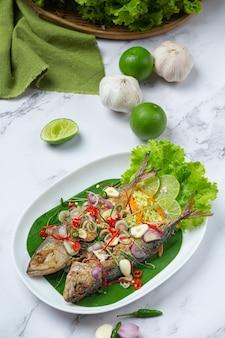 Scharfe und würzige makrele mit thailändischen zutaten dekoriert