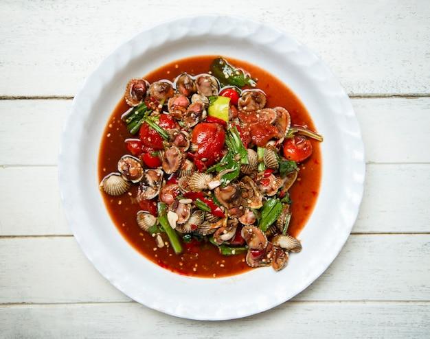 Scharfe und würzige muschelblutherzmuschelsalatmischung aus gemüse, tomaten, kräutern und gewürzen