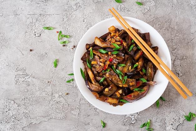 Scharfe würzige eintopf-aubergine im koreanischen stil mit frühlingszwiebeln. aubergine sautieren. veganes essen. flach liegen. draufsicht
