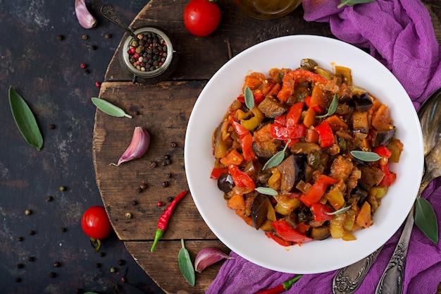 Scharfe würzige eintopf-auberginen, paprika, tomaten und kapern. flach liegen. draufsicht