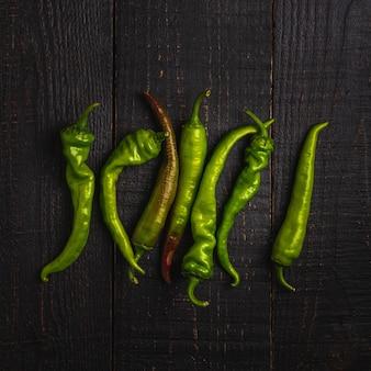 Scharfe würzige grüne chilischoten auf dunklem holztisch