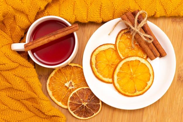 Scharfer aromatischer tee mit zimtstangen und getrockneten orangenscheiben. auf einem holztisch
