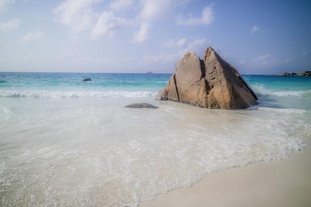 Scharfer felsen an einem strand, umgeben vom meer unter dem sonnenlicht in anse lazio in praslin, seychellen