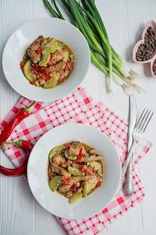 Scharfer salat mit hähnchen, zucchini und chili, bestreut mit sesam und kräutern. asiatisches essen. weißes holz .