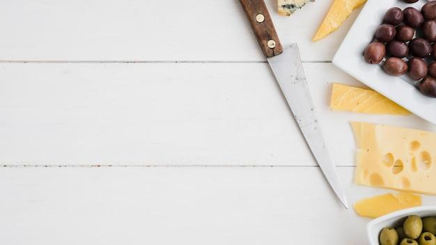 Scharfes messer mit käse und neuen oliven auf weißem hölzernem schreibtisch