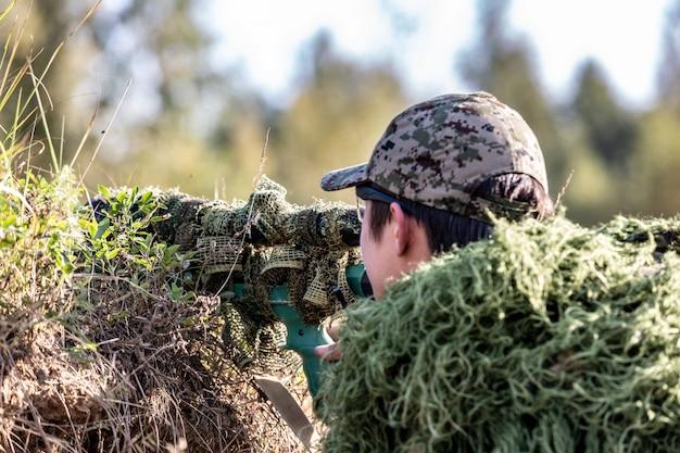 Scharfschütze, bewaffnet mit großkalibrigem scharfschützengewehr, schießt aus dem schutz auf feindliche ziele und sitzt im hinterhalt