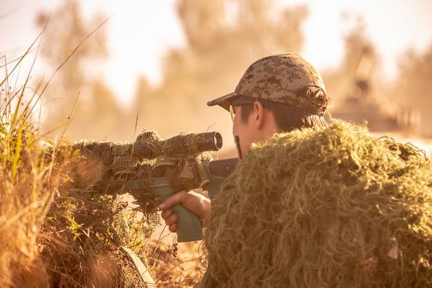 Scharfschütze mit großem kaliber, scharfschützengewehr bewaffnet, feindliche ziele aus der nähe des schutzes schießend, im hinterhalt sitzend