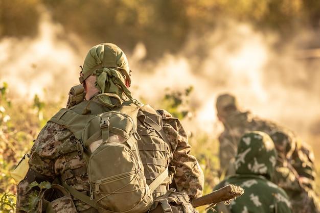 Scharfschützen-team, bewaffnet mit großkalibrigem scharfschützengewehr, schießt aus dem schutz auf feindliche ziele und sitzt im hinterhalt