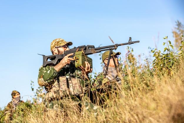 Scharfschützen-team mit großkalibrigem scharfschützengewehr, das feindliche ziele aus der nähe des schutzes schießt und im hinterhalt sitzt
