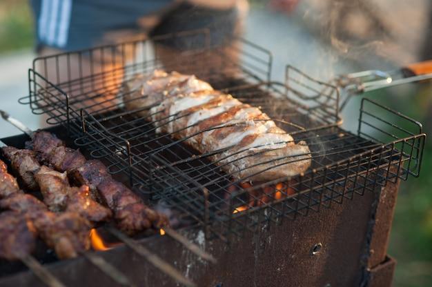 Schaschlik auf dem grill. marinierter schaschlik, der auf einem grill über holzkohle zubereitet.