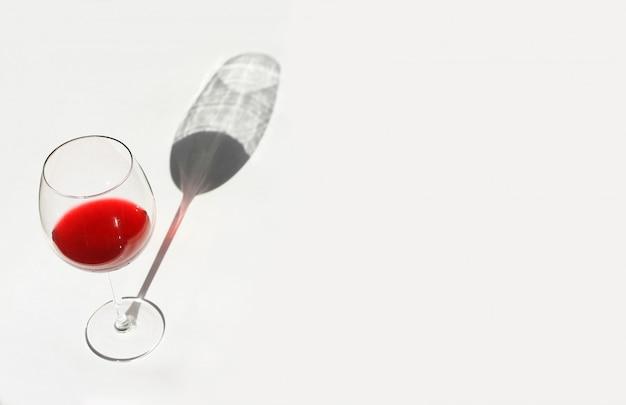 Schatten aus einem glas mit rotwein. minimales stilleben mit einem harten schatten.