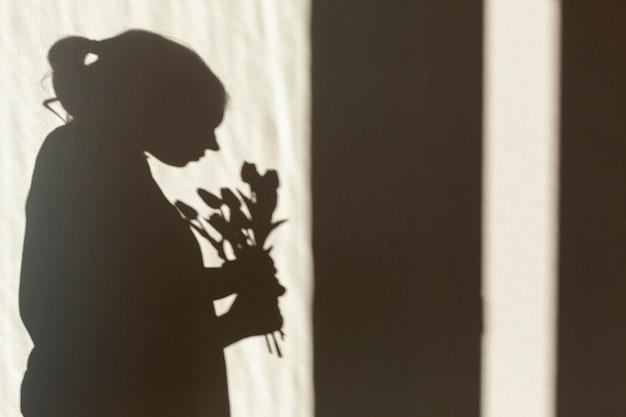 Schatten der frau, die blume hält