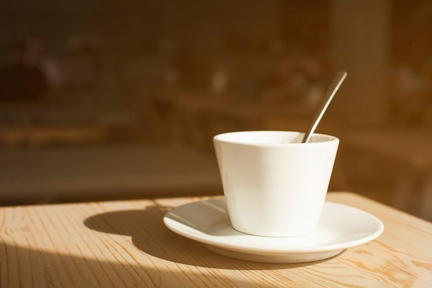 Schatten der kaffeetasse und der untertasse auf hölzernem schreibtisch