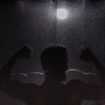Schatten des mannes, der muskeln zeigt
