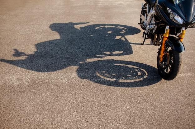 Schatten des orange motorrades auf asphalt