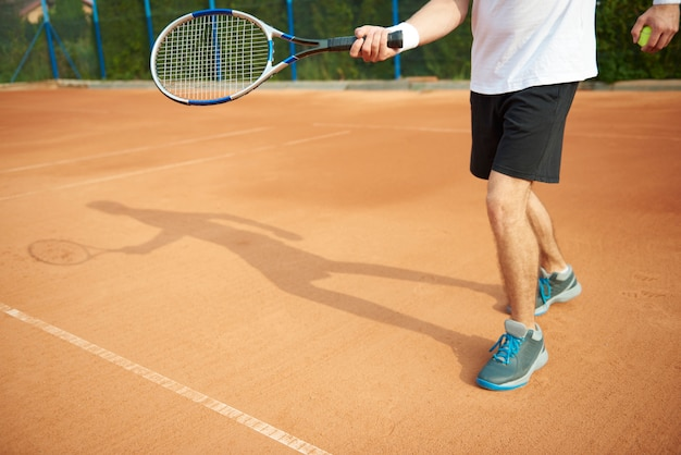 Schatten des tennisspielers auf dem platz