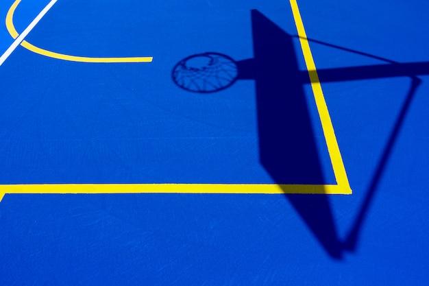 Schatten eines basketballkorbs auf dem boden des platzes