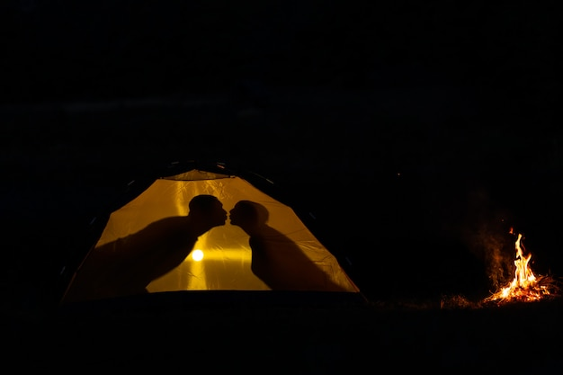 Schatten eines paares in den liebesküssen in einem touristischen zelt in der natur.