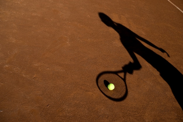 Schatten eines tennisspielers mit einer kugel