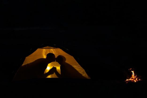 Schatten eines verliebten paares küsst in einem touristischen zelt in der natur. camping in der wildnis
