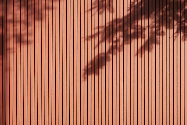 Schatten von blättern auf braunem lattenholz