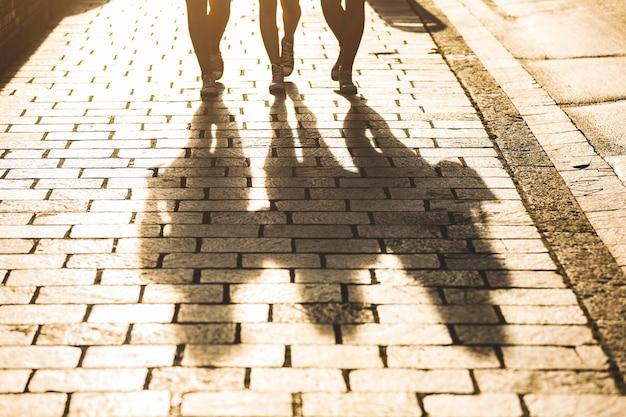 Schatten von drei mädchen, die auf einen bürgersteig in der stadt gehen
