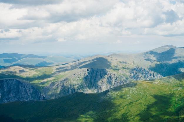 Schatten von wolken auf massiven grünen bergen