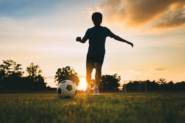 Schattenbild-aktionssport außerhalb des jungen mannes, der spaß hat, fußballfußball für übung unter dem sonnenuntergang spielend.