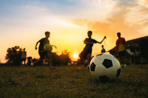 Schattenbild-aktionssport im freien eines kindes, das spaß hat, fußballfußball für übung unter dem sonnenuntergang zu spielen.