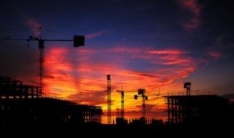 Schattenbild-Baustelle und Abbruchgebäude mit Sonnenunterganghintergrund.
