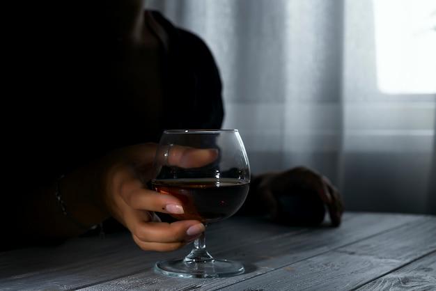 Schattenbild der anonymen alkoholischen frauenperson, die hinter glas alkohol trinkt.