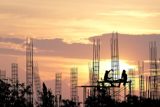 Schattenbild der arbeitskraft auf sicherheitsstand vom hochland und von der stahlstange an der baustelle.