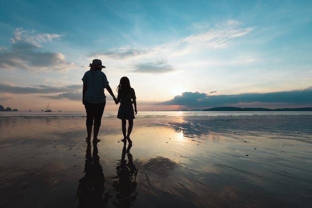 Schattenbild der asiatischen mutter und der tochter, die hand halten und zusammen auf dem strand zur sonnenuntergangszeit mit schönem meer und himmel gehen. familie genießen mit naturkonzept.