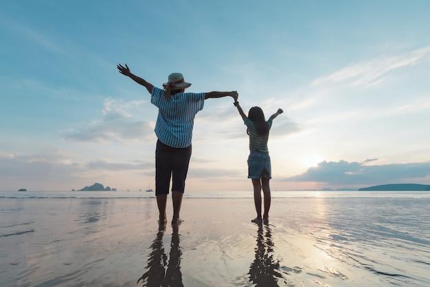 Schattenbild der asiatischen mutter und der tochter, die hand zusammenhalten, die am strand stehen und das schöne meer und himmel zur sonnenuntergangszeit betrachten.