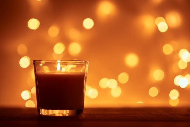 Schattenbild der brennenden kerze mit goldenen unscharfen lichtern